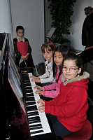 3 enfants de l'association musicale au piano